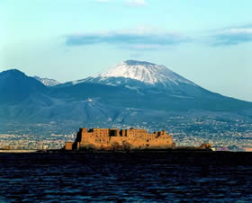 Castel dell'Ovo, a Norman masterwork, with an unusually snow-capped Vesuvius in the background - Credit - De Agostini Picture Library